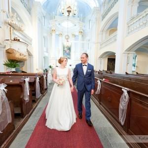 Przepiękne wnętrze kościoła uchwycone przez fotografa ślubnego z momencie gdy młoda para opuszcza kościół w Bielsku