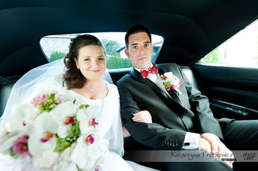 Uśmiechnięta młoda para w aucie jadącym na ceremonię, reportaż ślubny bielsko